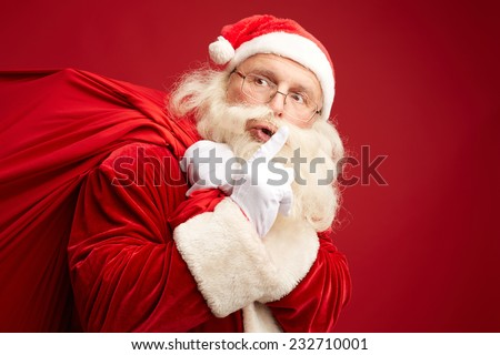 Moving Santa Claus with huge red sack keeping forefinger by his mouth - stock photo