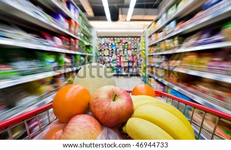 Moving shopping cart, and shot with a slow shutter from the shopper's point of view. The fruits in the shopping cart is in focus, and the supermarket is motion-blurred.