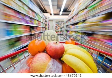 Moving shopping cart, and shot with a slow shutter from the shopper's point of view. The fruits in the shopping cart is in focus, and the supermarket is motion-blurred. - stock photo