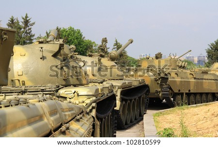 Moving tanks column against city trees and background - stock photo