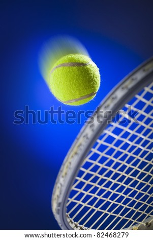 Moving tennis ball just about to be hit from the tennis racket  on blue background - stock photo