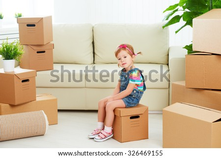 moving to a new apartment. happy child and a cardboard box - stock photo