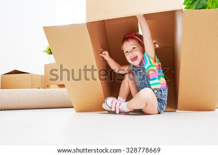 moving to a new apartment. happy child in a cardboard box