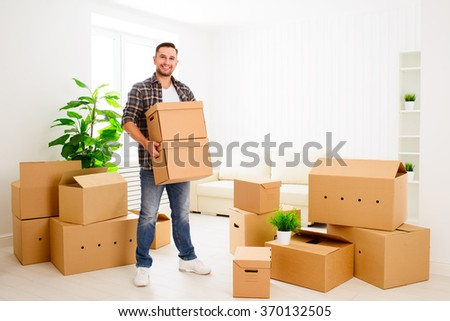 moving to a new apartment. Young happy man with cardboard boxes - stock photo