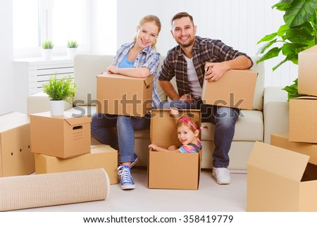 moving to a new home. Happy family with cardboard boxes - stock photo