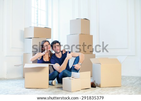 Moving to a new house and repairs in the apartment. Love couple sitting on a couch and hugging while a young and beautiful couple in love sitting in an empty apartment among boxes