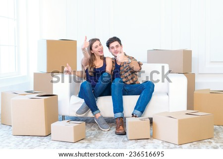 Moving to a new house and repairs in the apartment. Love couple sitting on the couch and show a thumbs up while young and beautiful couple in love sitting in an empty apartment among boxes