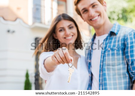 Moving to a new house. Beautiful young loving couple standing against house while woman holding key and smiling - stock photo