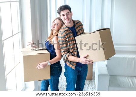 Moving to a new life. A girl and a guy holding boxes for moving the hands and smiling at the camera while a couple in love standing at the window among boxes - stock photo