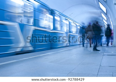 Moving train and passengers on subway station