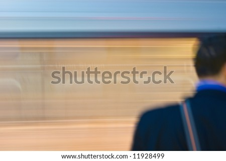 Moving Train and Waiting Passenger in Train Station - stock photo
