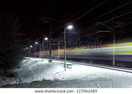 moving train at night in snow landscape - stock photo