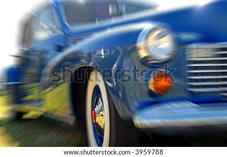 Moving Vintage Car with Focus on Shiny Hubcap - stock photo