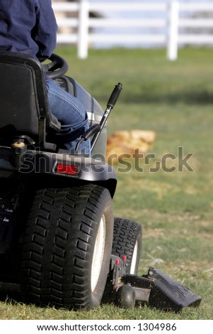 Mowing a large area with a riding lawnmower (shallow focus). - stock photo