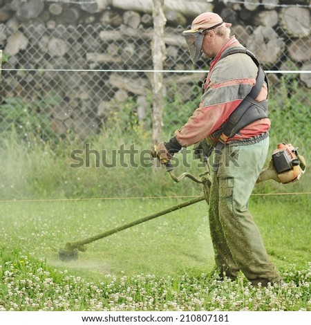 Mowing a lawn with a lawn mower  - stock photo