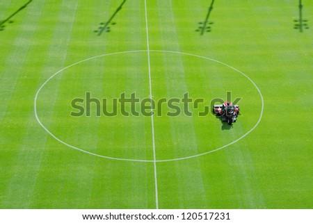 Mowing graass on the football stadium - stock photo