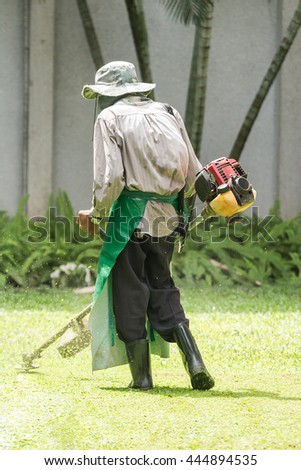 Mowing Grass. Human Man Cut Lawn Park Day Farm Tool Front Work Job Sod Turf Care Yard One Field Weed Hat Back Trim Motor Sward Plant Wall Hedge Hobby Power Blade Safety Farmer Nature Mower Engine - stock photo