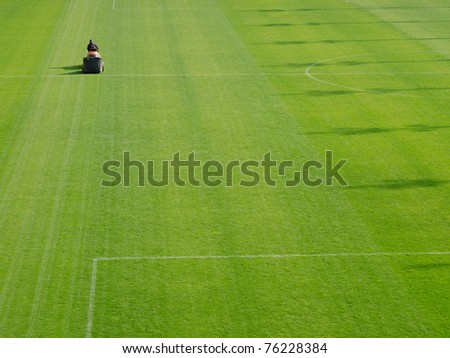 mowing grass in stadium - stock photo