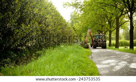 mowing grass shoulder or verge along road in public space  with big orange tractor mower  - stock photo