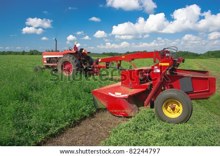 Mowing Hay:  A mower drawn beside a tractor cuts a field of alfalfa in southern Wisconsin - stock photo