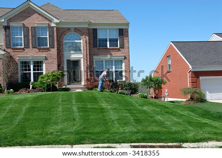 Mowing The Lawn - Professional lawn care service using a riding lawn mower to cut the grass. - stock photo
