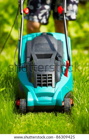 Mowing the lawn with new modern mower - stock photo