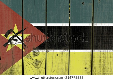 Mozambique flag on wooden background - stock photo