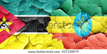 Mozambique flag with Ethiopia flag on a grunge cracked wall - stock photo