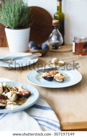 Mozzarella and fresh figs with dressing of balsamic vinegar, olive oil and honey served as appetizer. Selective focus - stock photo