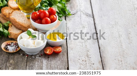mozzarella and ingredients for the salad on a wooden background, horizontal - stock photo