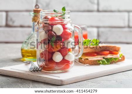 Mozzarella and tomato salad Caprese in a jar for lunch. - stock photo