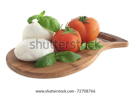Mozzarella, basil, and tomatoes on a cutting board - isolated on white - stock photo
