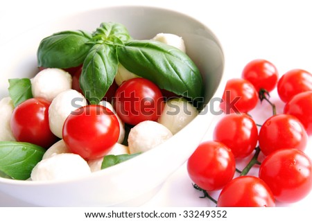 Mozzarella boconccini cheese balls with cherry tomatoes and green fresh basil in a salad bowl on white blur background - stock photo