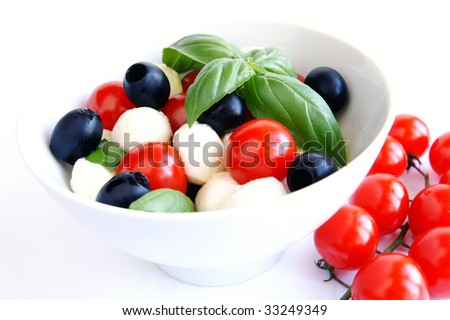 Mozzarella boconccini cheese balls with cherry tomatoes, black olives and green fresh basil in a salad bowl on white blur background - stock photo