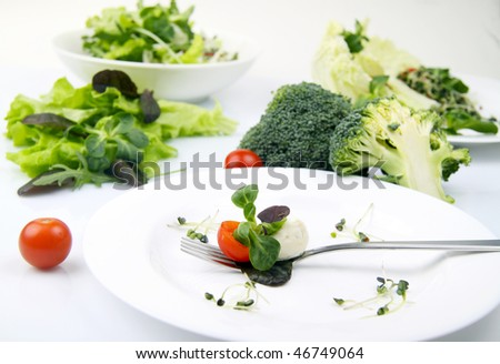 mozzarella cheese and basil leaf on fork - stock photo