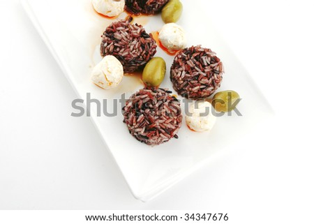 mozzarella cheese and dark rice served on plate