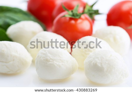 mozzarella cheese balls and a ripe cherry tomatoes and greens on the white background. horizontal format - stock photo