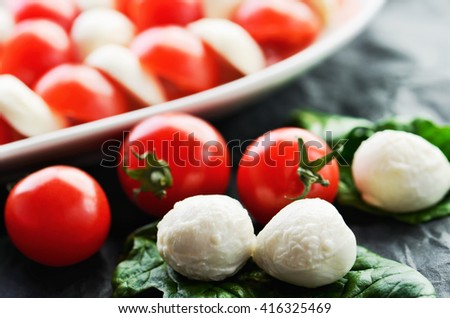 mozzarella cheese balls, ripe cherry tomatoes and caprese salad in a dish on the dark background close-up. horizontal format - stock photo
