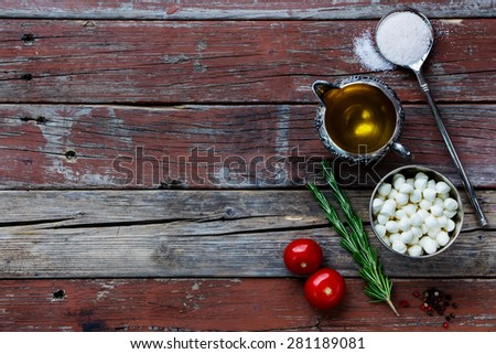 Mozzarella cheese, tomatoes and olive oil on rustic wooden background. Lots of copy space. Vegetarian food, health or cooking concept. - stock photo
