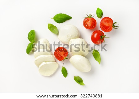 mozzarella, cherry tomatoes and fresh basil - ingredients for caprese salad - stock photo