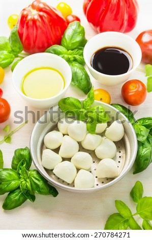 Mozzarella in bowl with basil leaves,oil,tomatoes and balsamic vinegar, italian food ingredients, close up - stock photo