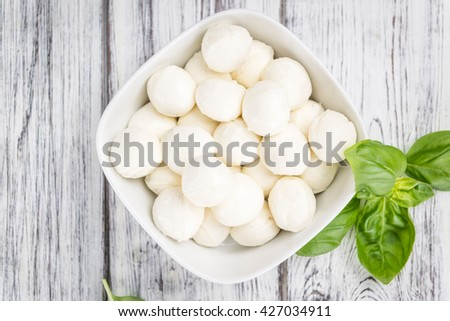Mozzarella (on wooden background; selective focus) as close-up shot