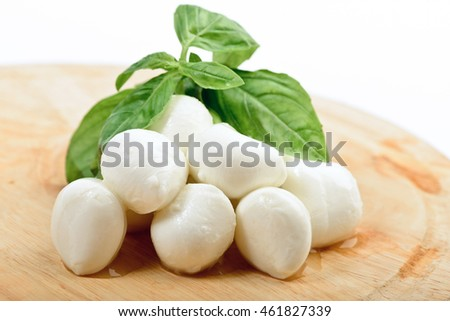 Mozzarella on wooden board with basil