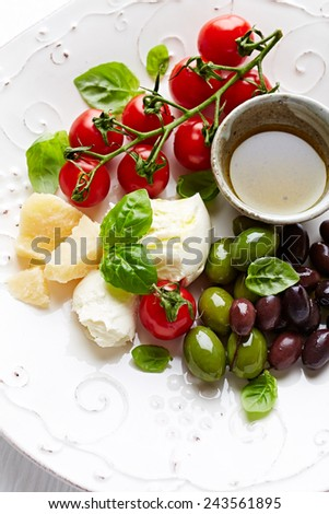 Mozzarella, parmesan, cherry tomatoes and olives (antipasti) - stock photo