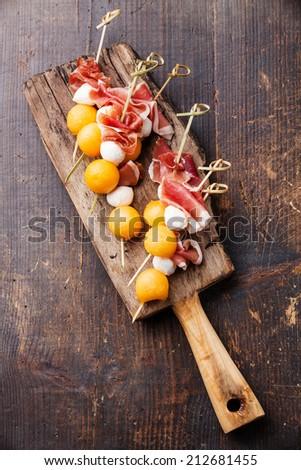 Mozzarella, prosciutto, melon canapes on dark wooden background - stock photo
