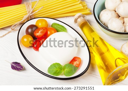 Mozzarella, tomatoes, basil and olive oil on wooden table - stock photo