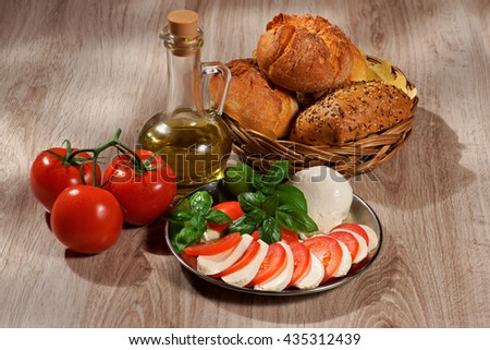 Mozzarella, tomatoes, olive, basil, roll, composition on a wooden table - stock photo