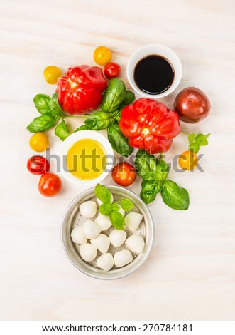 Mozzarella tomatoes salad ingredients with basil leaves,oil and balsamic vinegar, preparation on white wooden background, top view - stock photo