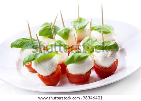 mozzarella with tomatoes and basil on white background - stock photo