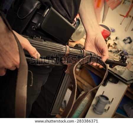 MP38 in the hands of a master restorer in the interior locksmith gunsmith. instagram image retro style - stock photo